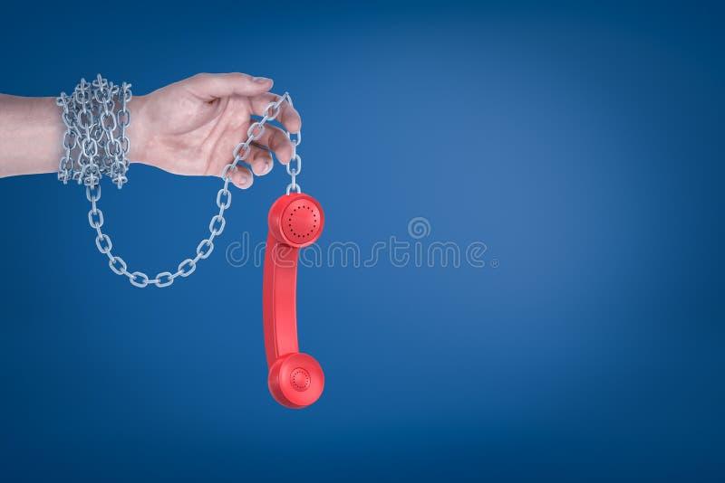 Männliche Hand verkettet an roten Retro- Telefonhörer auf blauem Hintergrund lizenzfreie stockfotografie