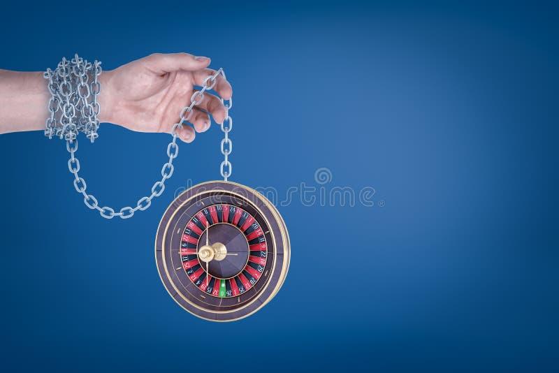 Männliche Hand verkettet an Roulette auf blauem Hintergrund lizenzfreies stockfoto