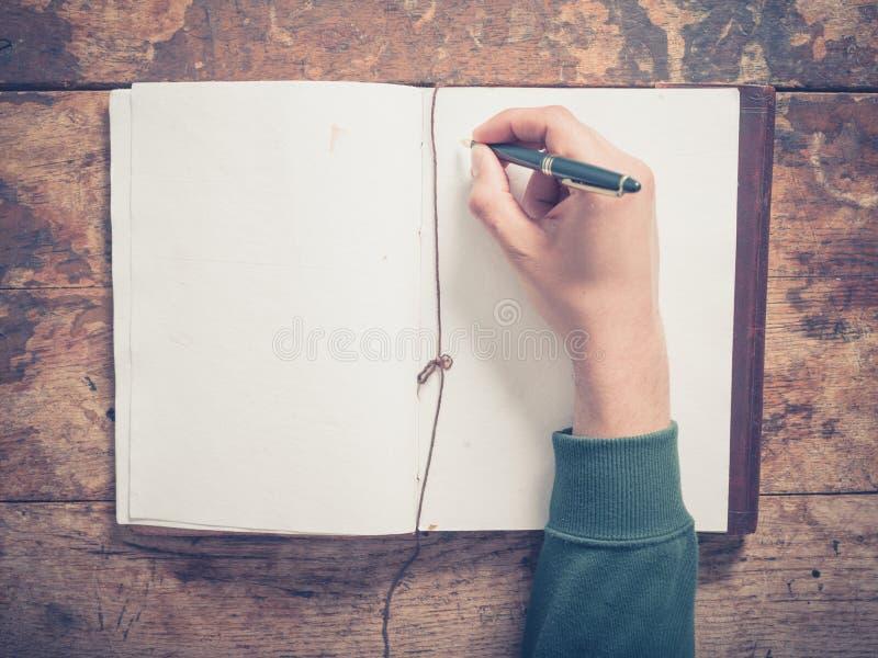 Männliche Handschrift im Notizblock lizenzfreie stockfotografie