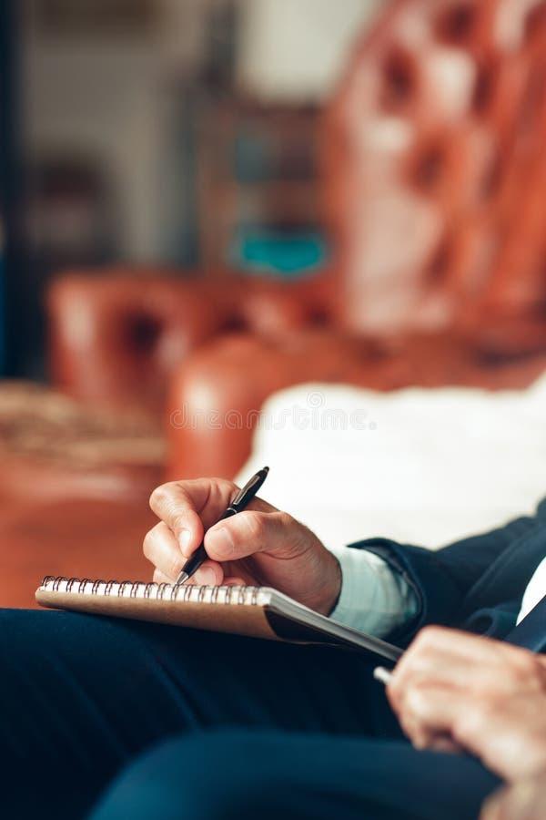 Männliche Handschriftpläne in einem Notizblock stockfoto