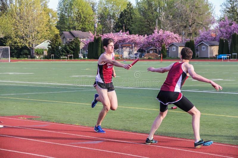 Männliche Highschool Athleten führen den Taktstock im Relais 4 X.400 in einem Bahntreffen stockbild