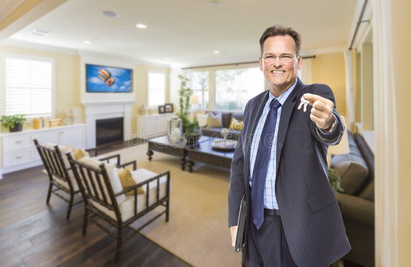 Männliche Immobilienagentur Holding Keys im schönen Wohnzimmer lizenzfreies stockfoto