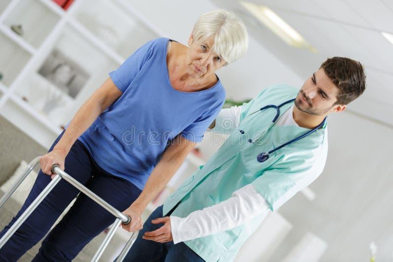 Männliche Krankenschwester, die arbeitsunfähiger älterer Dame mit gehendem Rahmen hilft stockbild