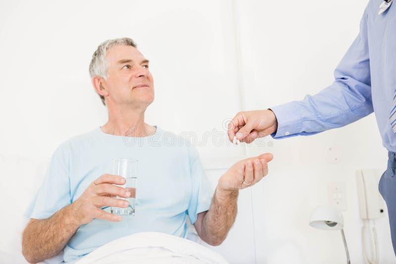 Männliche Krankenschwester, die dem älteren Mann Pillen gibt lizenzfreies stockbild