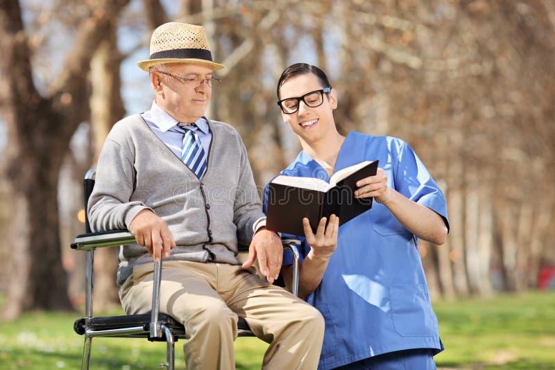 Männliche Krankenschwester, die ein Buch zu einem älteren Mann in einem Rollstuhl liest lizenzfreies stockbild