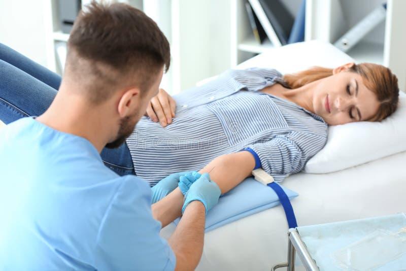 Männliche Krankenschwester, die weiblichen Spender für Bluttransfusion im Krankenhaus vorbereitet lizenzfreie stockbilder