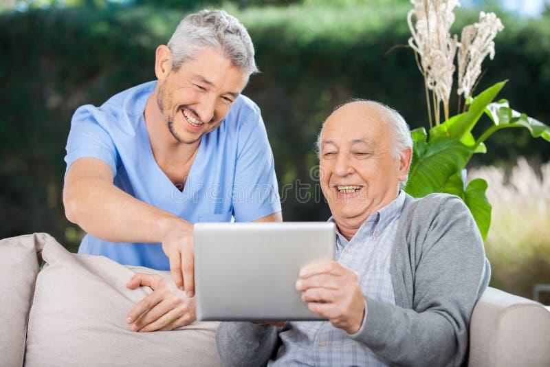 Männliche Krankenschwester lachendes And Senior Man bei der Anwendung lizenzfreie stockbilder