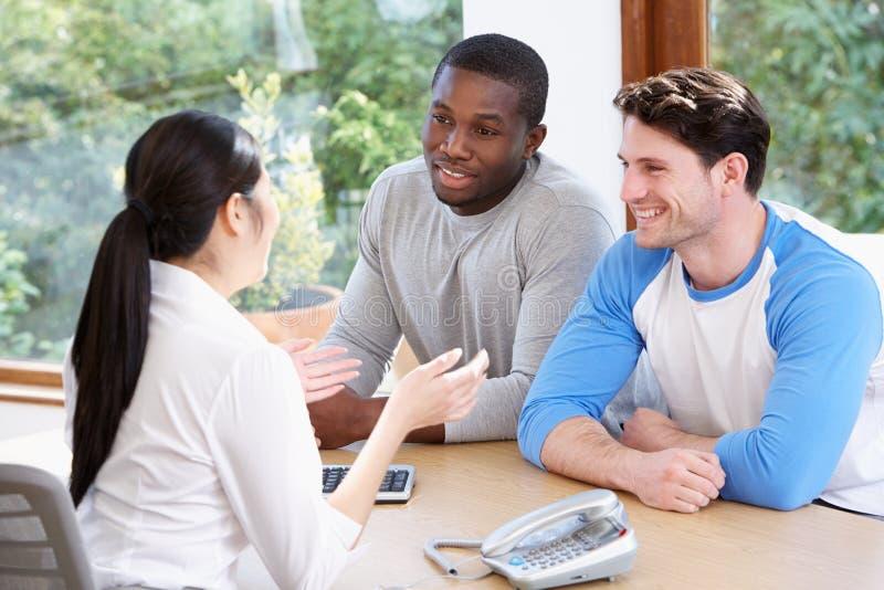 Männliche Paare, die mit Finanzberater im Büro sprechen lizenzfreie stockfotos