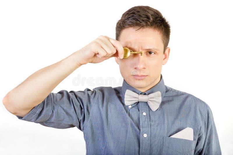 Männliche Person, die Schlüsselweißen übermäßighintergrund hält stockfoto