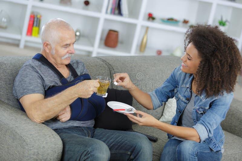 Männliche Pflegekraft, die arbeitsunfähigem männlichem Pensionär hilft stockbild