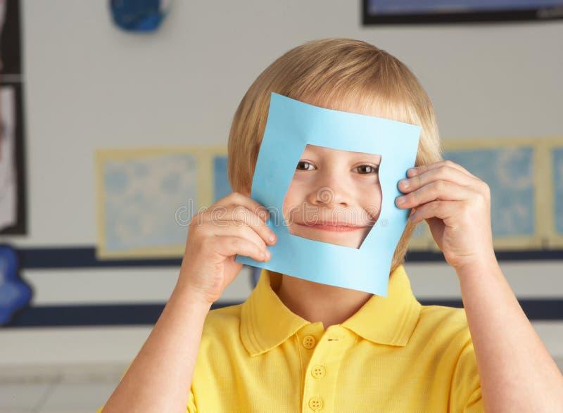 Männliche Primärschule, die Papierformen herausschneidet stockfotos