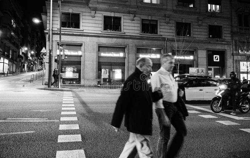 Männliche Senioren, die Straße nachts in Barcelona kreuzen stockfotografie