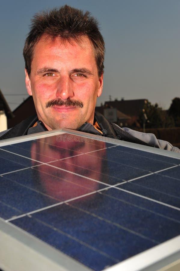 Männliche Solararbeitskraft installieren Sonnenkollektoren auf Haus lizenzfreie stockfotos