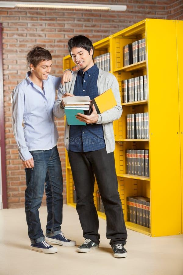 Männliche Studenten, die Buch in der College-Bibliothek betrachten lizenzfreie stockfotos