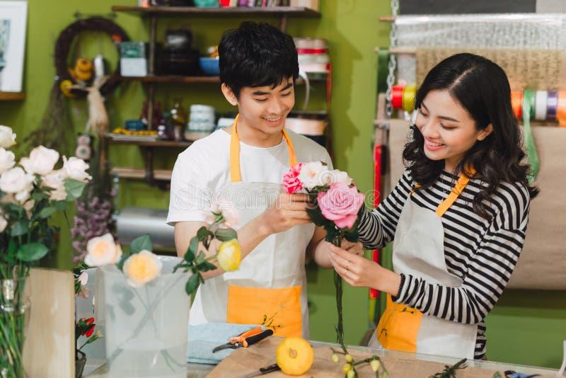 Männliche und weibliche Floristen mit schönen Blumensträußen im Blumenladen stockbild