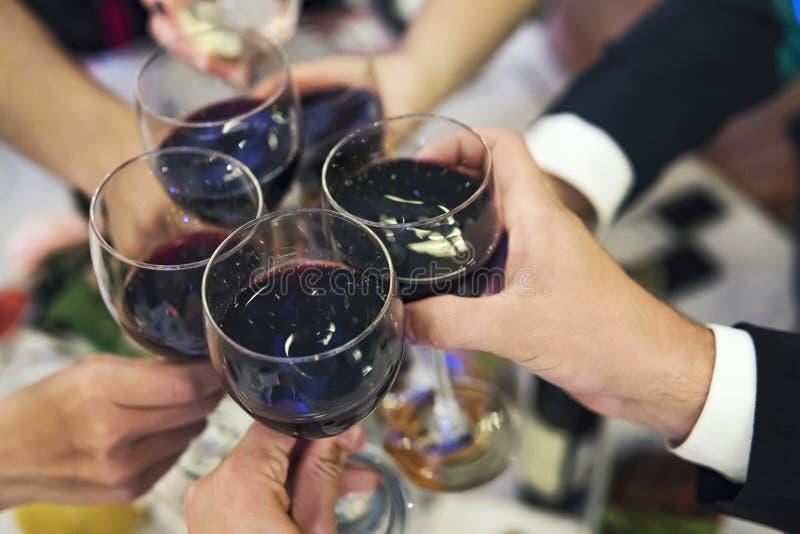 Männliche und weibliche Hände mit gefüllten Gläsern Rotwein über der Restauranttischplatte Trinkende Toast und klirrende Trommeln lizenzfreies stockbild