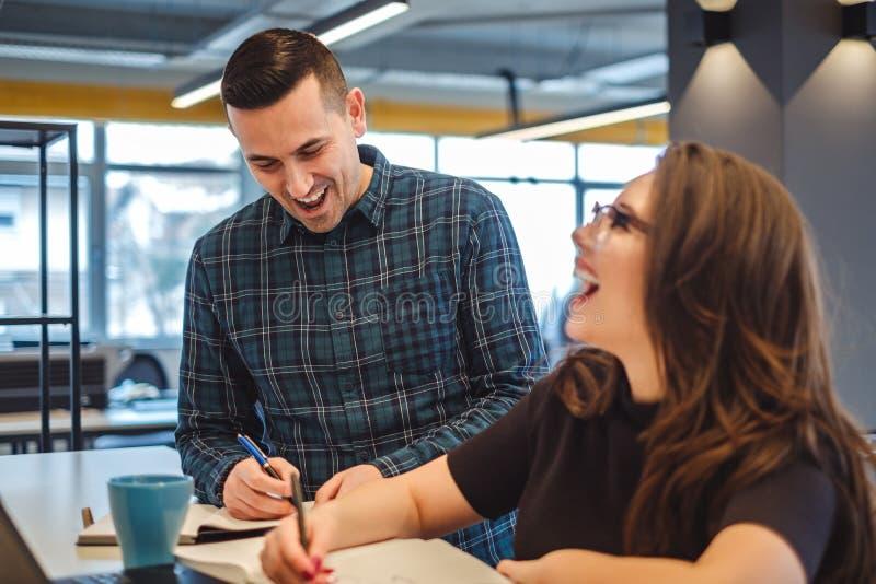 Männliche und weibliche Kollegen, die im Büro lachen stockbild