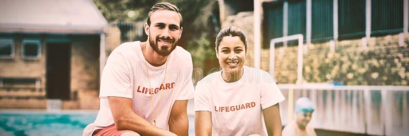 Männliche und weibliche Leibwächter, die Rettungsdosen am Poolside halten lizenzfreie stockfotografie