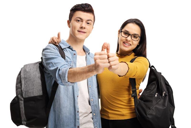 Männliche und weibliche Schülerinnen, die Daumen hochhalten stockfotografie