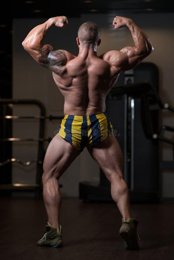Männliche vorbildliche Posing In The-Turnhalle mit Muskeln stockbilder