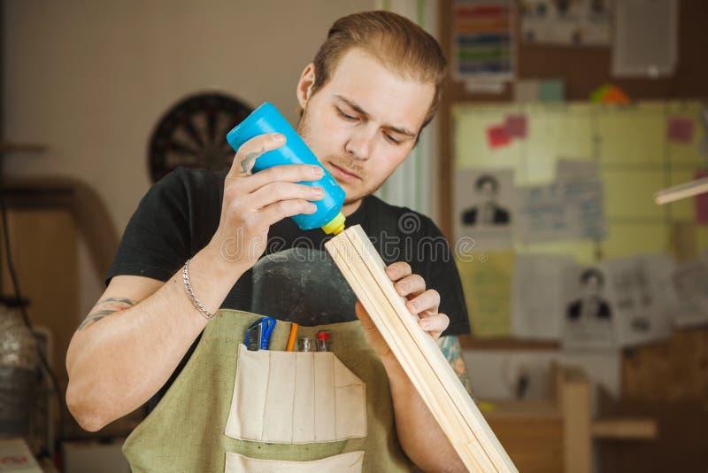 Männlicher Abstrich mit hölzerner Planke des Klebers an der Werkstatt Männliches Arbeiten stockfoto
