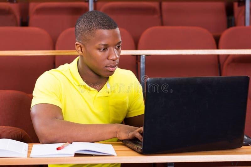 Männlicher afrikanischer Hochschulstudentlaptop stockfoto