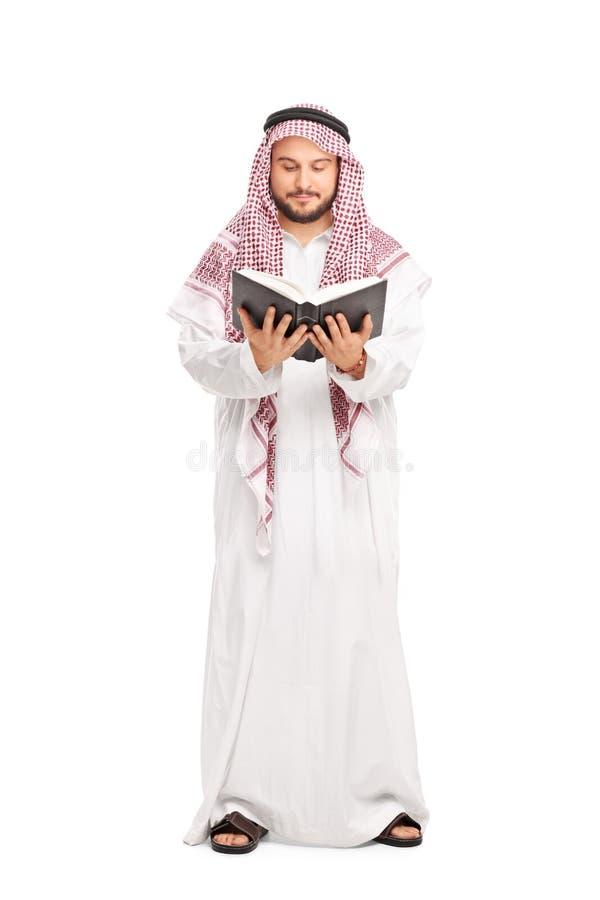 Männlicher Araber in einer weißen Robe ein Buch lesend stockfotografie