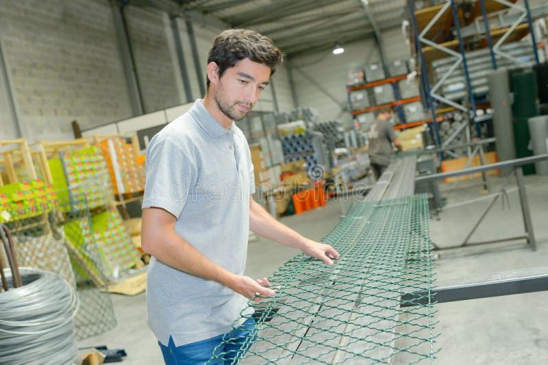 Männlicher Arbeiter, das Fechten produzierend stockbild