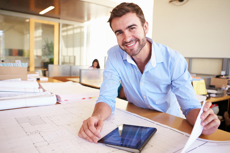 Männlicher Architekt With Digital Tablet, das Pläne im Büro studiert lizenzfreies stockbild