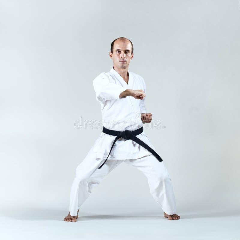 Männlicher Athlet bildet formale Karateübung aus stockfotografie