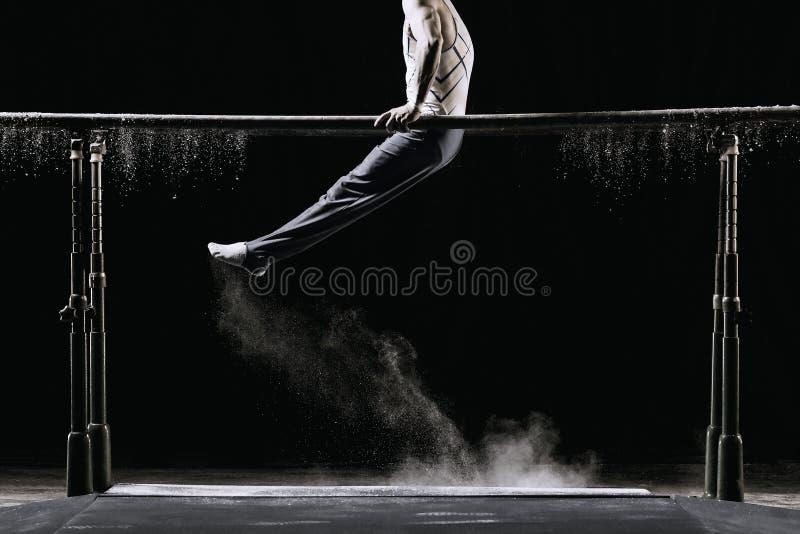 Männlicher Athlet, der Handstand auf gymnastischem Barren mit Talkum durchführt Lokalisiert auf Schwarzem stockbilder