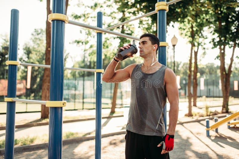Männlicher Athlet trinkt Wasser nach Training im Freien stockfotos