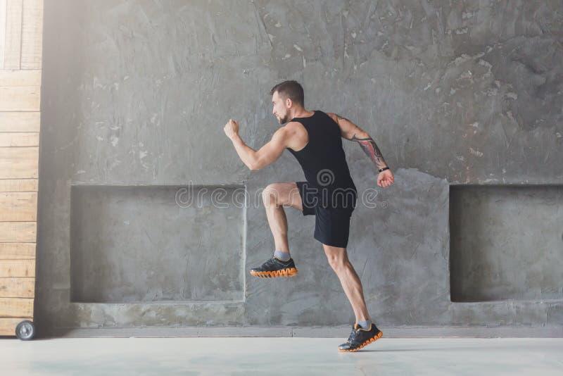 Männlicher Athletensprinterbetrieb, zuhause trainierend stockfotografie