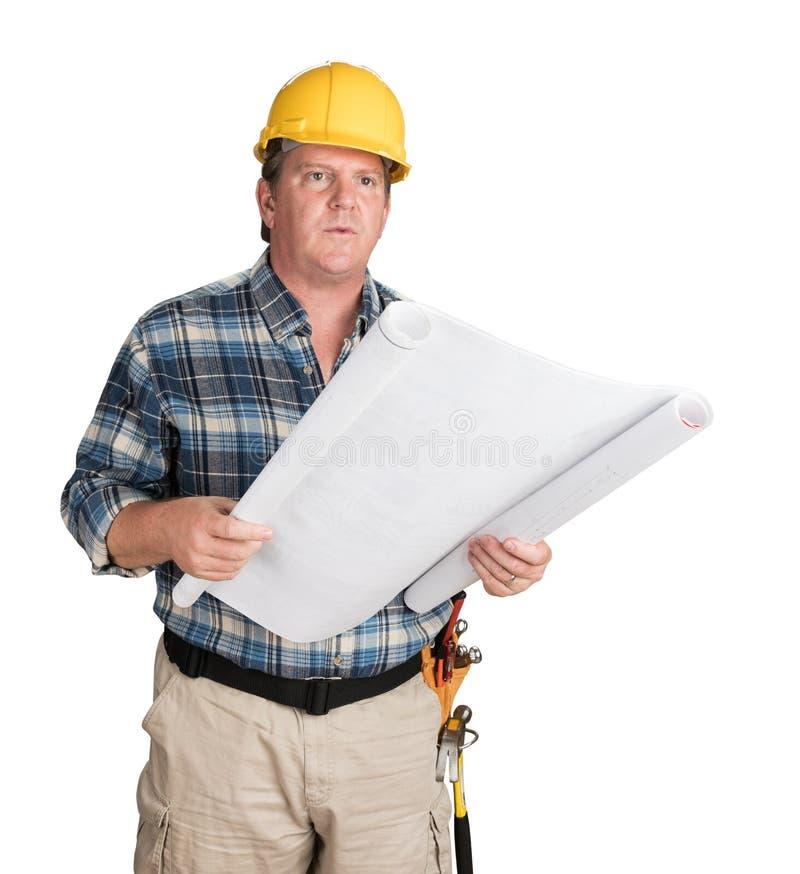 Männlicher Auftragnehmer mit den Haus-Plänen, die den Schutzhelm lokalisiert auf Weiß tragen stockfotografie
