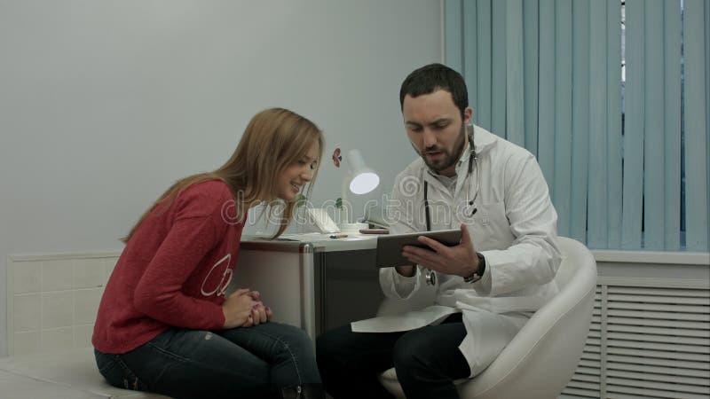 Männlicher bärtiger Doktor konsultieren Kunden mit Tabletten-PC lizenzfreie stockfotos