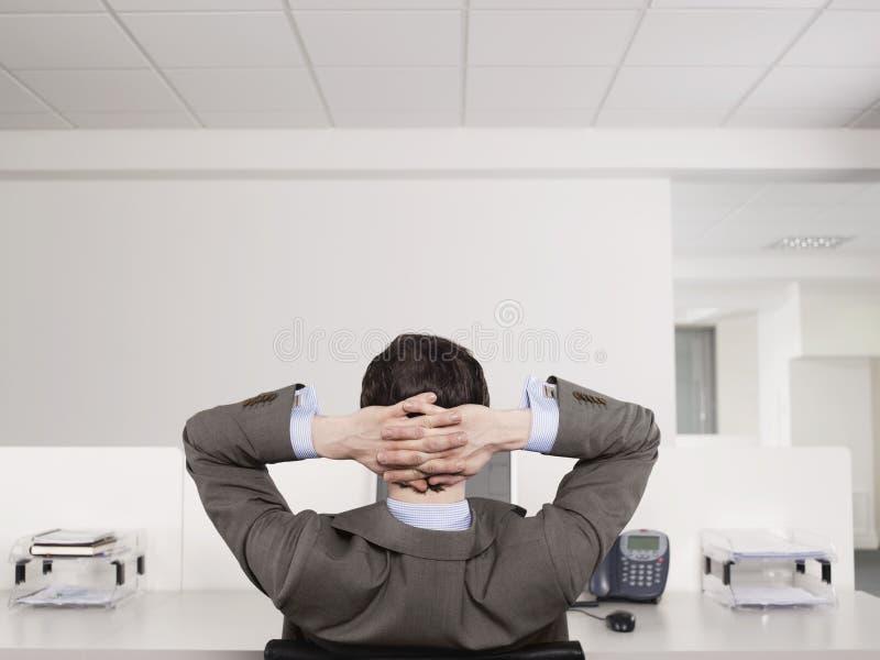 Männlicher Büroangestellter, der am Schreibtisch sich entspannt lizenzfreie stockfotos