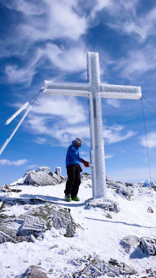 Männlicher backcountry Skifahrer auf einem hohen alpinen Gipfel, der sich vorbereitet, in das Logbuch hängt auf das Gipfelkreuz z stockfotos