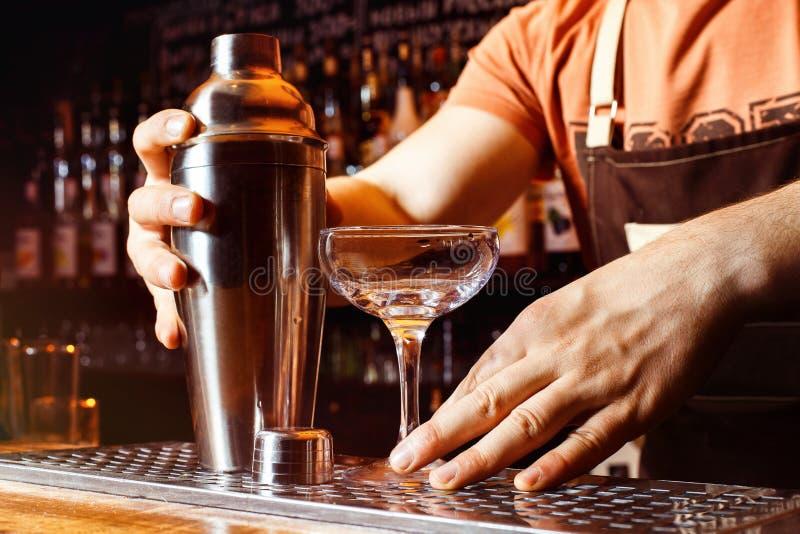 Männlicher Barmixer macht das Cocktail, das Schüttel-Apparat an der Bar hält lizenzfreie stockbilder