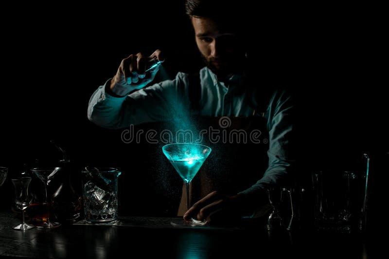 Männlicher Bartender bespritzt mit einem Bitter auf einem blauen alkoholischen Cocktail in einem Martini-Glas mit Spikelet stockbilder