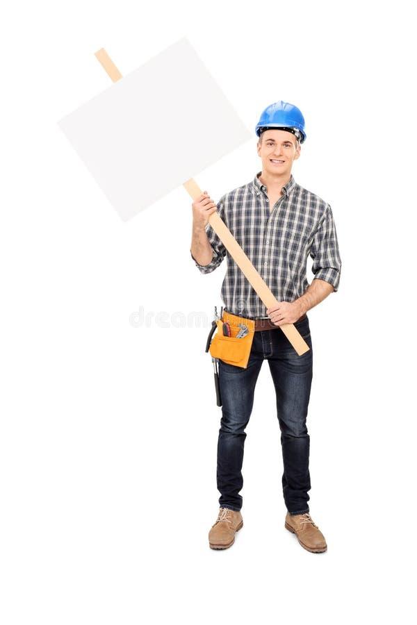 Männlicher Bauarbeiter, der ein leeres Zeichen hält stockfoto
