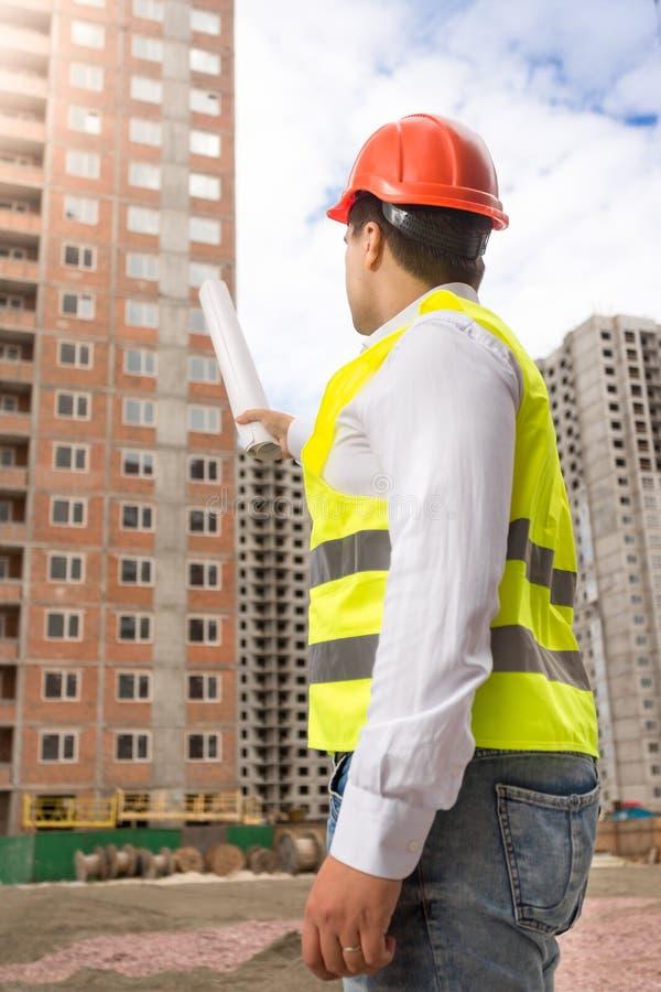 Männlicher Bauingenieur, der im Bau mit Plänen auf neuem Haus zeigt stockbild