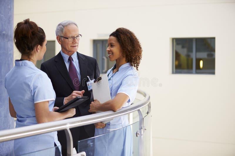 Männlicher Berater Meeting With Nurses, das Digital-Tablet verwendet lizenzfreies stockfoto
