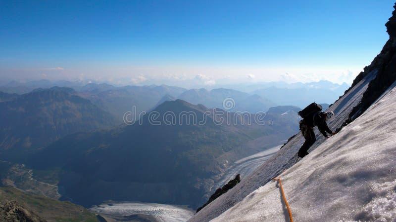 Männlicher Bergsteiger auf einem steilen und herausgestellten Eisfeld lizenzfreies stockbild