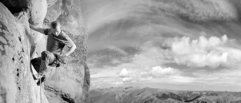 Männlicher Bergsteiger, der großen Flussstein in der Natur mit Seil klettert stockbild