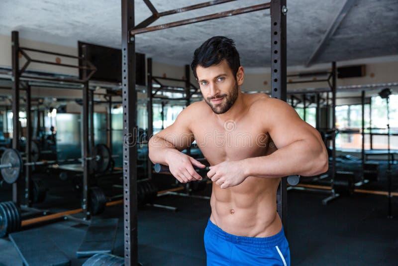 Männlicher Bodybuilder, der nahe Barren stillsteht stockbild