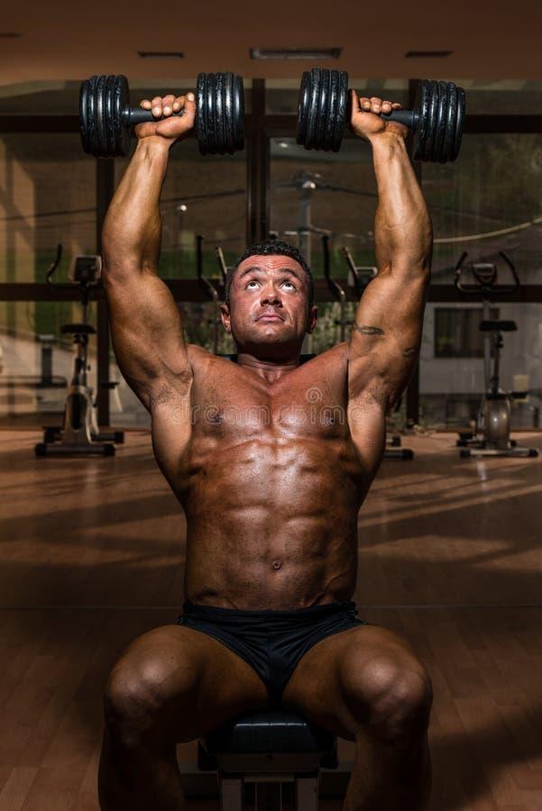 Männlicher Bodybuilder, der Schulterpresse Whitdummkopf tut lizenzfreies stockbild