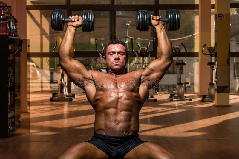Männlicher Bodybuilder, der Schulterpresse Whitdummkopf tut stockfotos