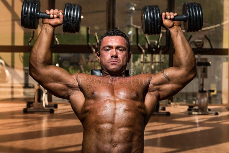 Männlicher Bodybuilder, der Schulterpresse Whitdummkopf tut lizenzfreie stockfotografie