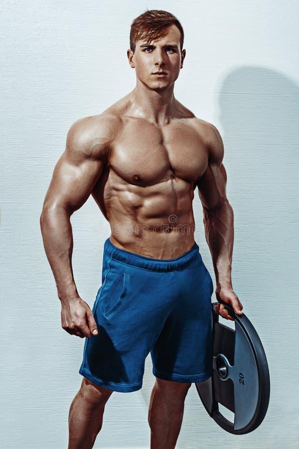 Männlicher Bodybuilder, Eignungsmodell bildet in der Turnhalle aus stockbild
