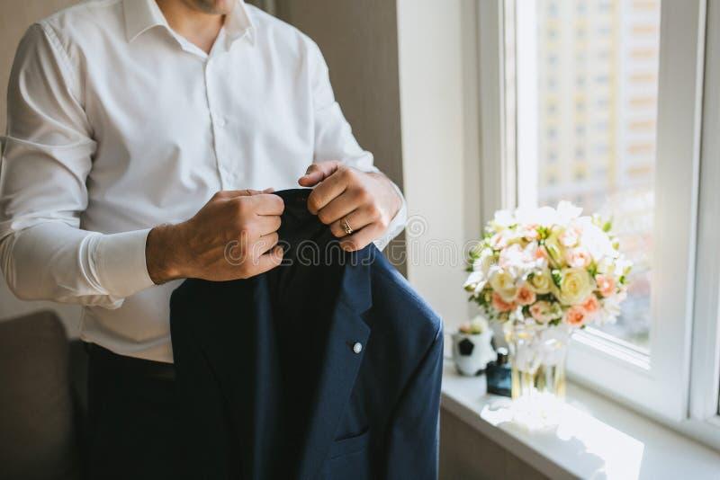 Männlicher Bräutigam in einem weißen Hemd hält eine blaue Hochzeitsjacke morgens stockfotos